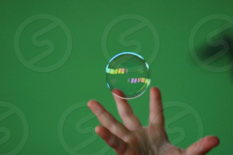 person tries to grab floating bubble photo