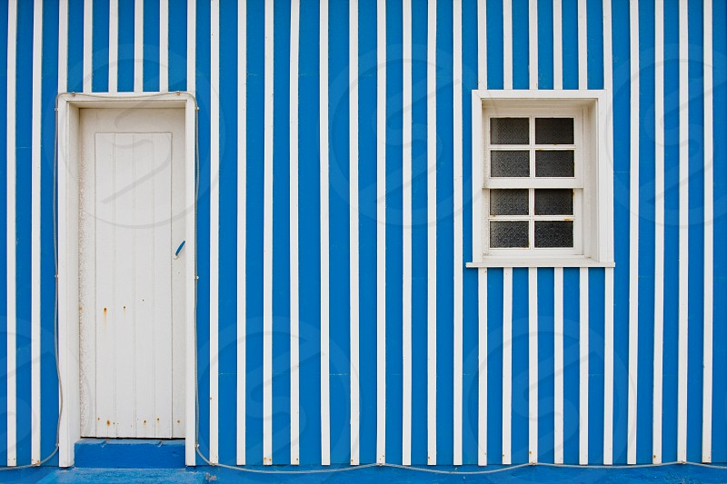 a wooden house in Portugal with blue and white stripes featuring the front door and a small window. photo