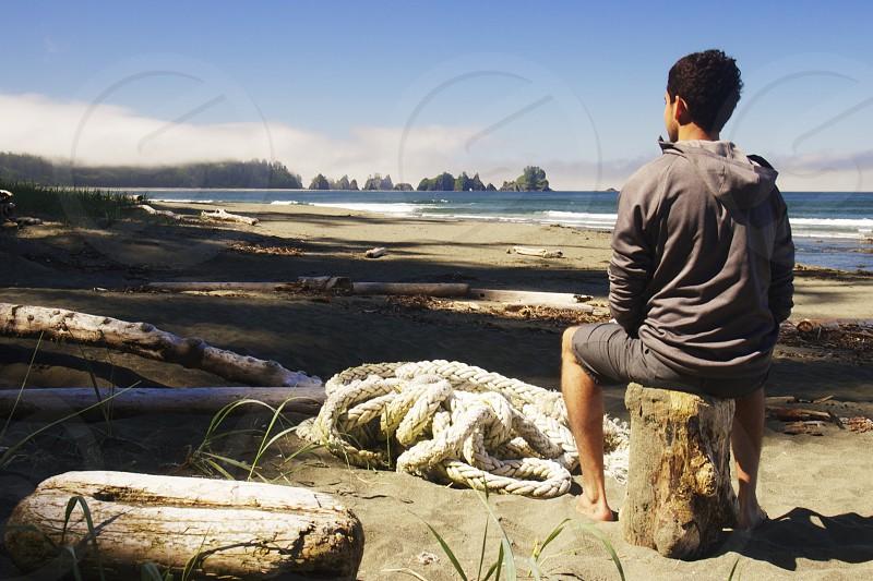man in grey hoodie sitting on brown log photo