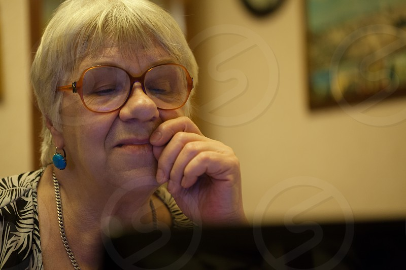 Thoughtful senior woman with blond hair wearing spectacles reading a computer screen with her hand to her face and an expression of concentration photo