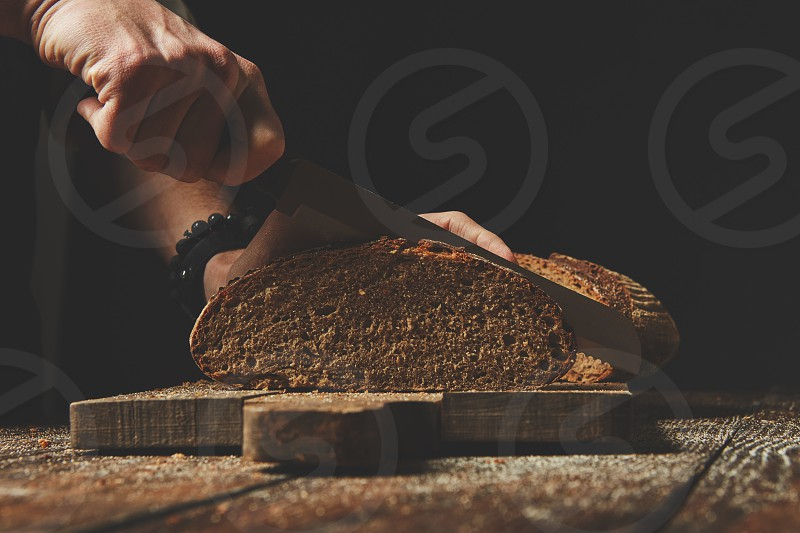 Close-up of male hands slice organic fresh bread on wooden board photo