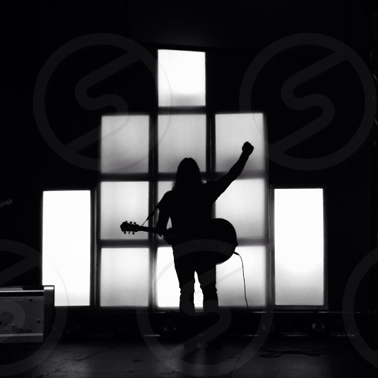 silhouette of man holding a guitar photo
