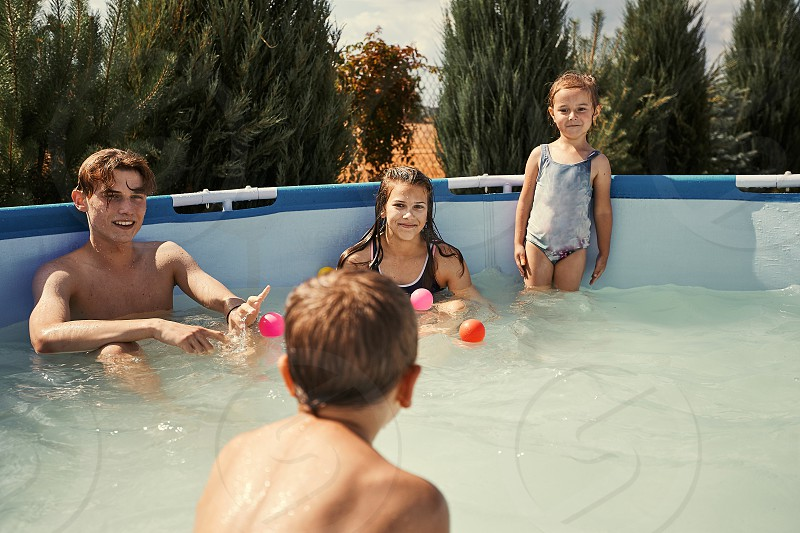 Children splashing jumping playing in a pool in backyard on summer vacation day. Real people authentic situations photo