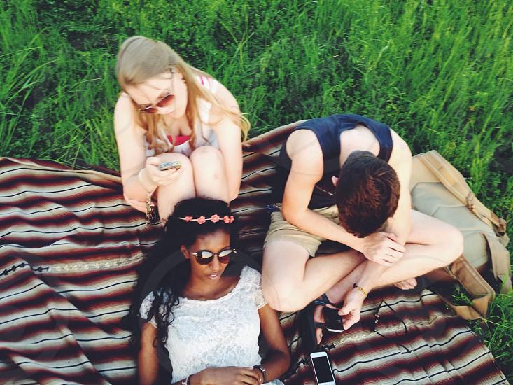 three people resting on grass field photo