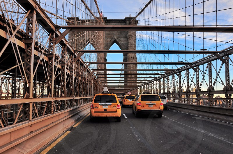 yellow taxi vans on cable-stayed suspension bridge under blue and white cloudy sky photo