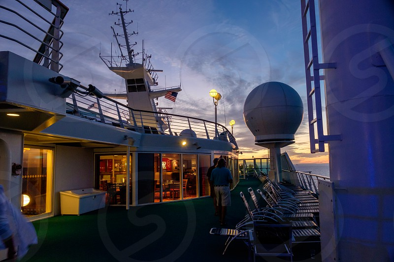 Near dark view of front of cruise ship showing tower and radar balls. photo
