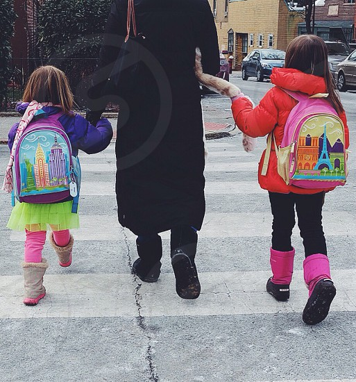 woman in black coat holding hands of two kids while crossing the street photo