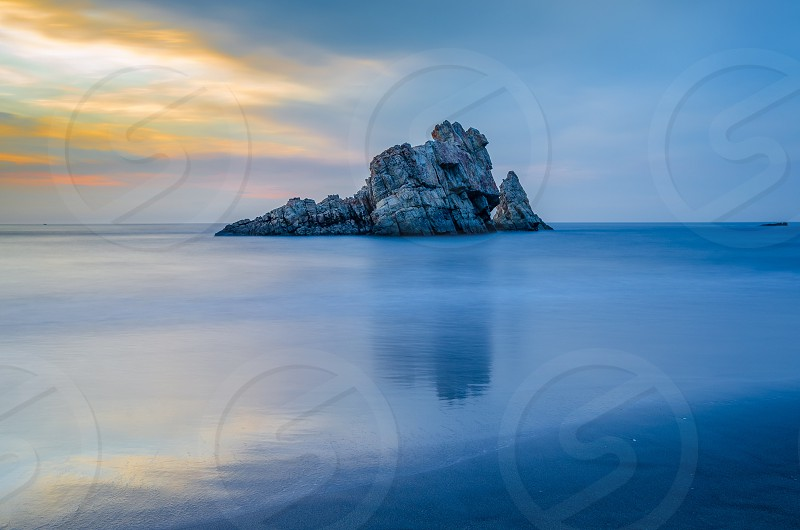 waves sunset rock sea ocean beach blue horizon photo
