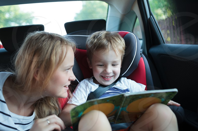 Little boy in a car sitting in child safety seat looking at the pictures in the book mother watching him photo