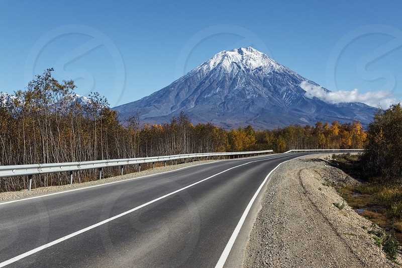 Autumn view of the asphalt road to the active Koryaksky Volcano on Kamchatka Peninsula on a sunny cloudless day with blue skies. Russia Far East. photo