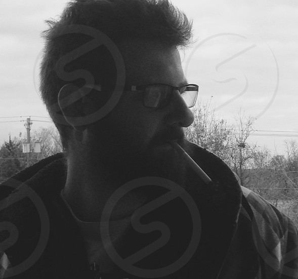 Bearded man smoking cigarette outside on a winter day. photo
