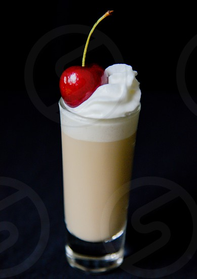 latte in drinking glass on top with whip cream and cherry photo