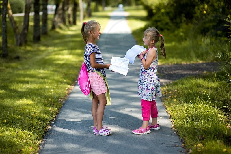 Two schoolgirls cheking exercise books photo