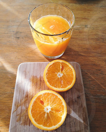 two slices of orange near glass of juice on wood table photo
