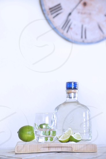 clear liquid in clear pint glass between clear blue lid glass bottle and green lime photo