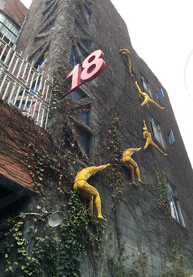 Arturban artpeopleyellow peoplewall18Abstract Yellow Figures on Building Shenzhen China street art Exterior building Shenzhen urban street art Brick Wall Artistic urbaninstallation art urban art art figures ArtWork four people  photo