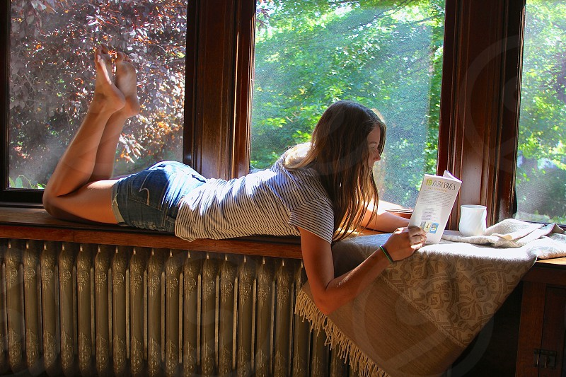 woman laying on her tummy reading book photo