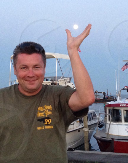 man wearing gray crew-neck shirt with his hands on the sun photo