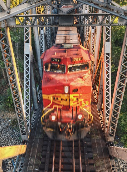 red and yellow train engine on grey metal trestle bridge over grey stone gravel and green trees photo
