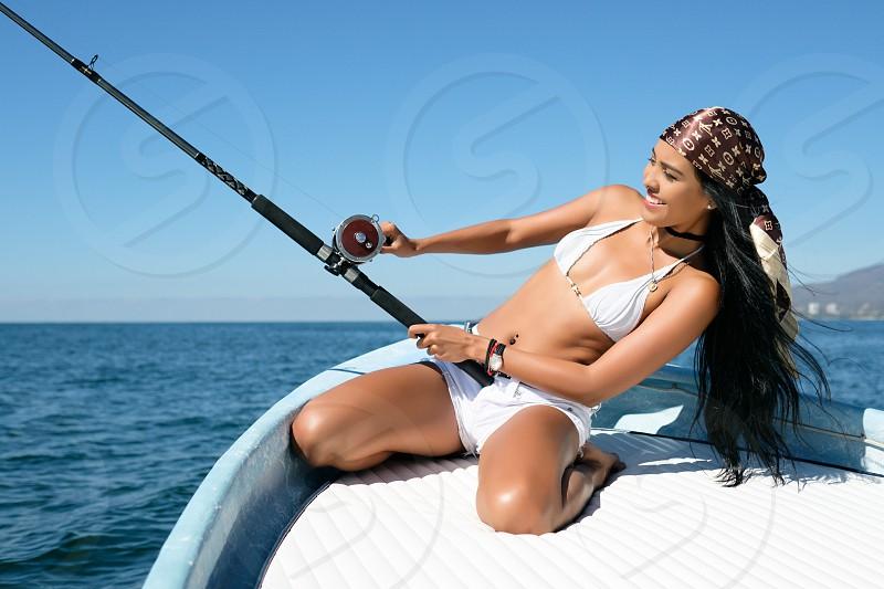 Young attractive latina woman having fun at fishing off a boat photo