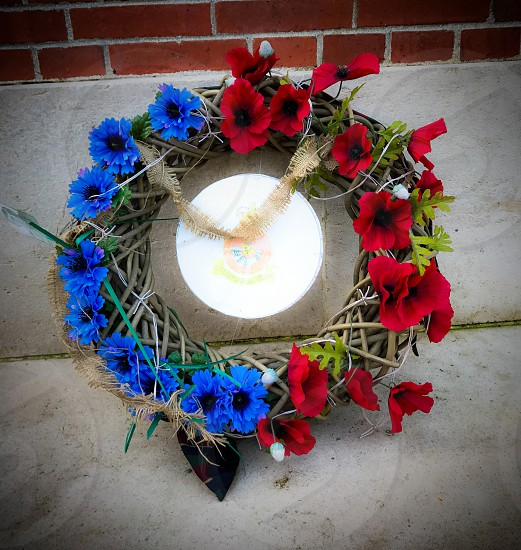 Outdoor day square colour Thiepval France Somme western front Battle site battleground historic historical red poppy flowers remembrance commemoration monument respect stone WWI WW1 World War One First World War Memorial carved carving masonry  country crucifix cross blue Wreath flowers woven photo