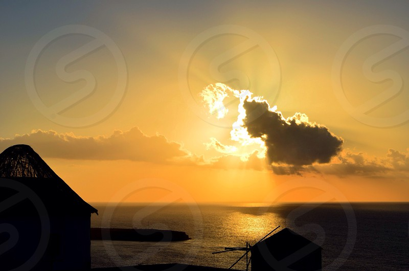 silhouette of building under clouds during golden hour photo