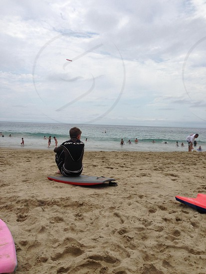 person in a black wetsuit sitting on a surfboard  photo