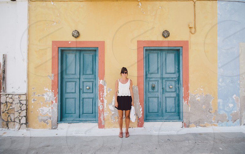 woman in white sleeveless top beside 2 blue door photo