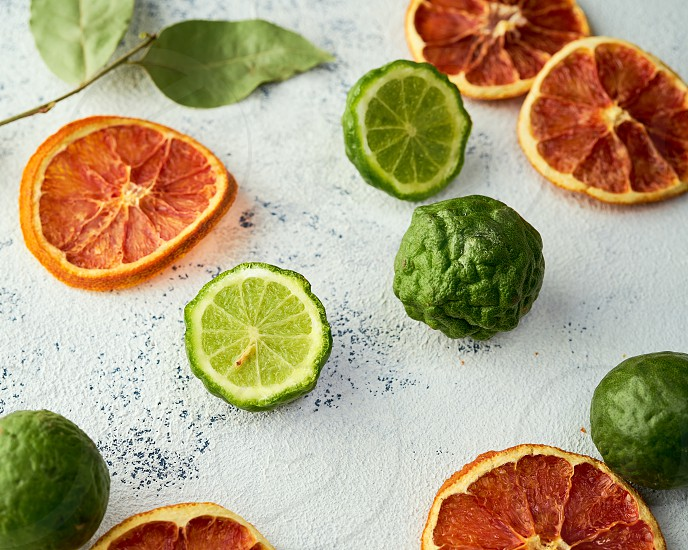 Fresh limes and orange chips on a light colored textured background                                photo