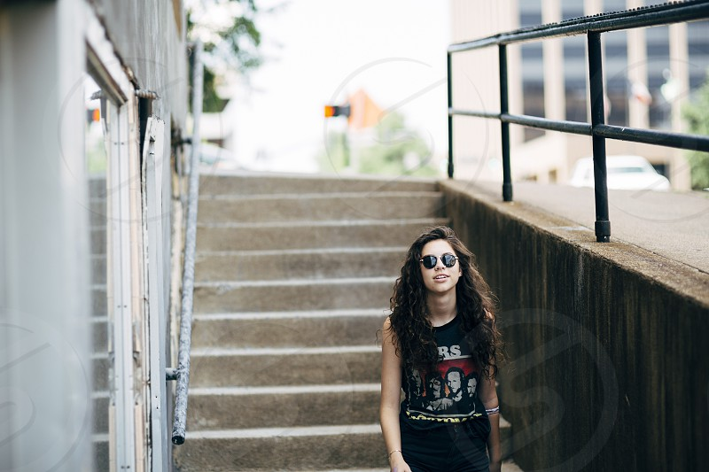 woman in black white and red sleeveless band t shirt walking down concrete staircase outside building photo