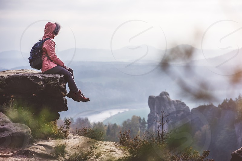 Young woman in outdoor clothing with backpack sitting on cliff's edge enjoying view of mountain ridge forest and river in the valley. Travel lifestyle concept. photo