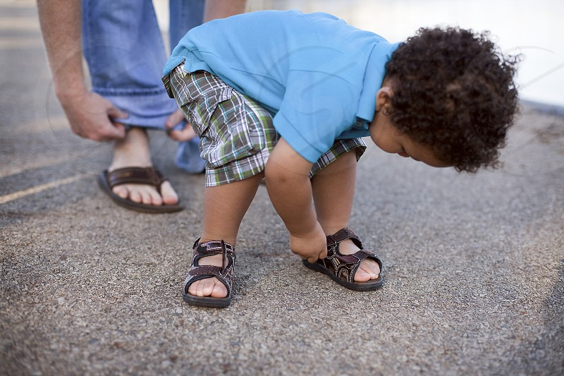 Toddler taking shoes off with dad in back photo