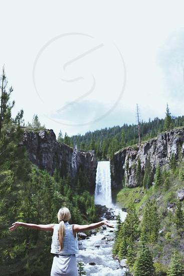 woman in bleached denim vest near waterfall photo