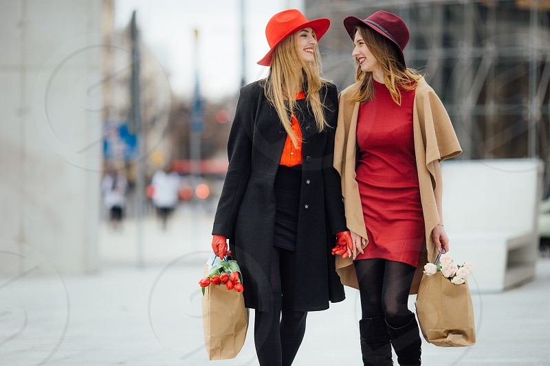 woman in black coat holding paper bag of red flowers walking together with woman in red dress holding paper bag of white flowers photo