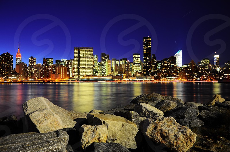 close up photo of brown boulders in front of body of water with background of lighted skyscraper buildings in the middle of urban area under blue dark sky during night time photo