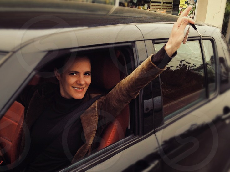 woman inside black car holding her keys outside the window smiling photo