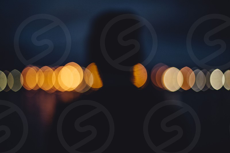 silhouette lights bokeh dark dusk twilight river mysterious figure man anonymous stranger photo