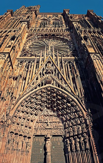 The Gate of Roman Catholic Cathedral Notre Dame of Strasbourg in Alsace France. Beautiful sunny day with clear blue sky. Majestic gothic architecture. photo