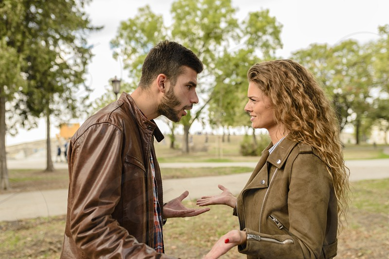 Young lovers arguing and trying to solve relationship problems in the public park. Negative emotions. photo