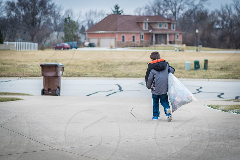 Little boy taking trash bag out to curb. photo