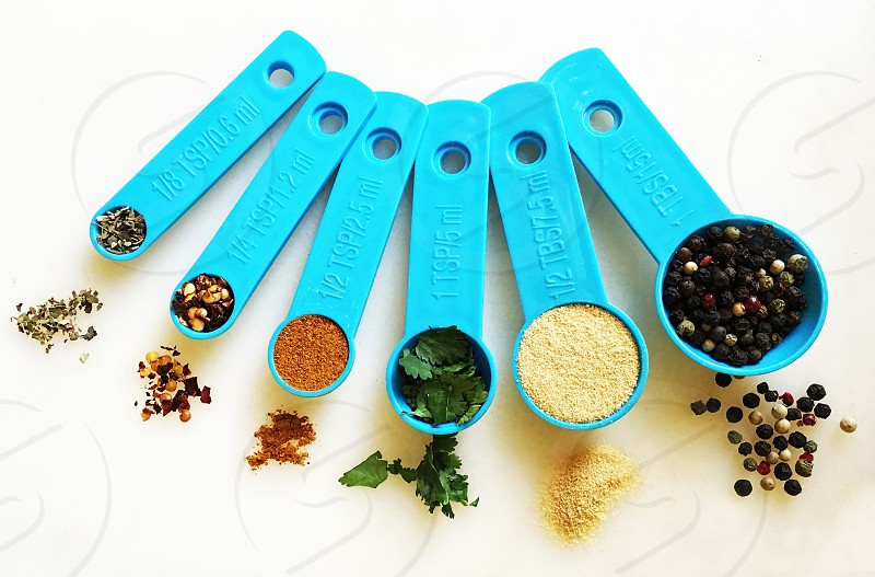 On white seen from above a set of graduated measuring spoons are filled with spices and herbs. photo