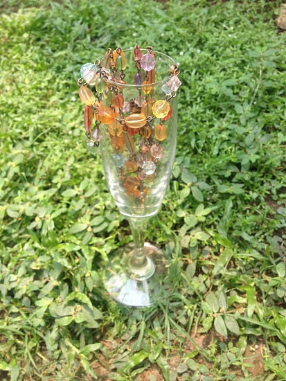 beaded jewelry on glass cup photo