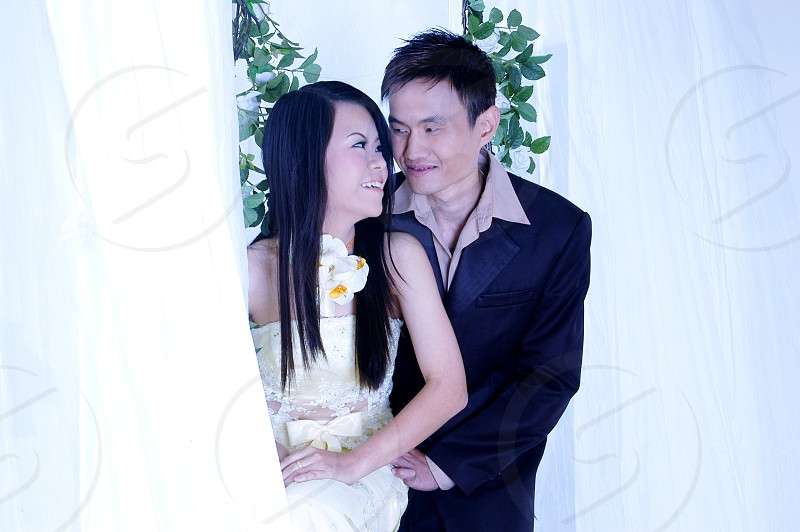woman in white wedding gown next to man in black formal suit jacket photo