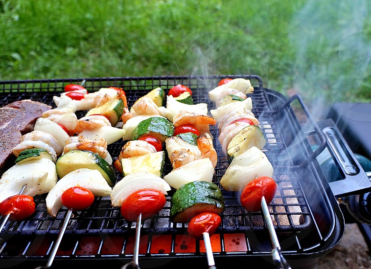 Barbecue zucchini mushrooms tomatoes steak meat shrimp gas smoke summer time grass food fire. photo