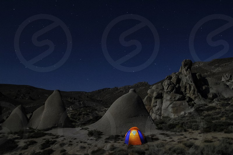 blue and orange tent with light inside beside gray stone in the dessert during night ime photo