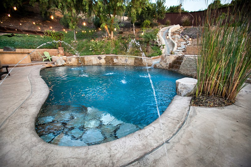 Luxurious backyard with a firepit swimming pool jacuzzi outdoor kitchen water spouts water slide and luscious vegetation. photo