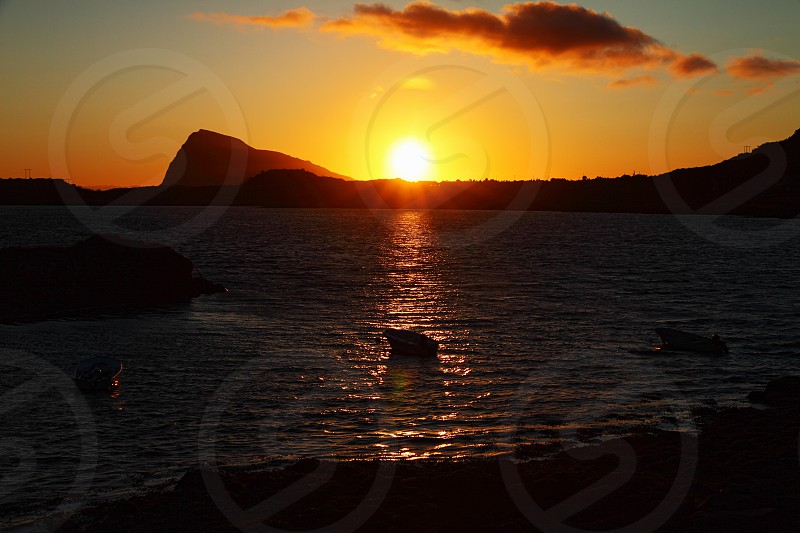 A few boats in the middle of the sea during the midnight sun in Lofoten Islands Norway.  Photo taken in summer 2011. photo