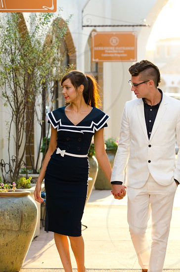 Couple Caucasian young woman young man walking holding hands love well dressed outdoors natural light love looking away blue dress white suit photo