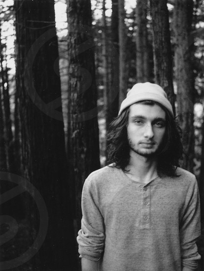 man wearing knit cap and henley shirt standing on forest grayscale photography photo