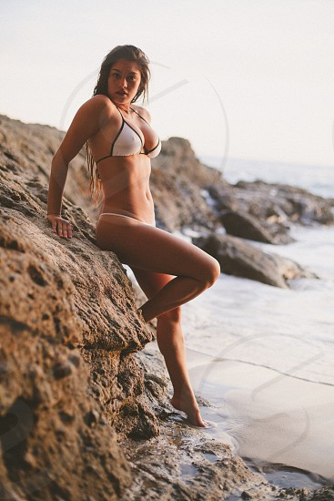 woman in 2 piece suit standing on rock photo